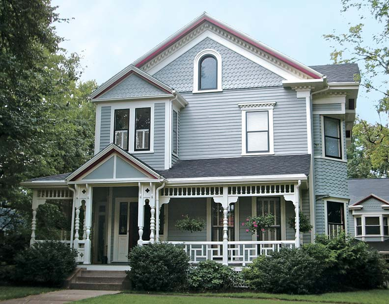 Consistent treatment of shingles on the gables—and a different one on the midsection of the bay wrapping around the corner—help dress up the exterior of this Queen Anne, despite a unified paint scheme.