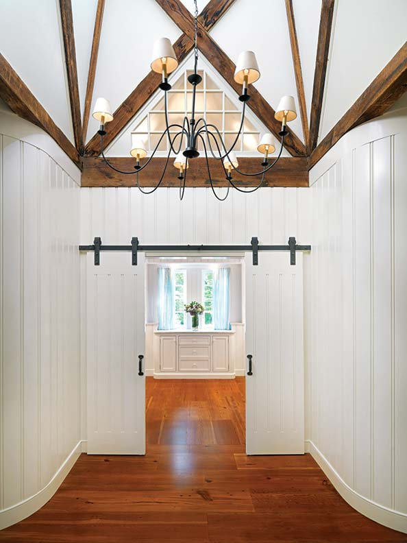 The master suite offers period touches such as wide vertical board, exposed framing, and wide plank flooring.