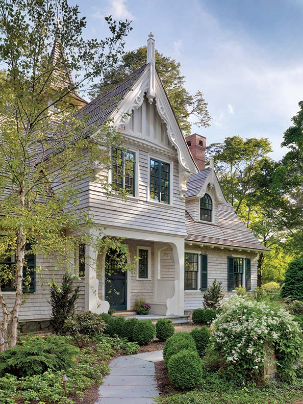 The gingerbread detailing in the house's eaves and dormers is welcoming and offers a charming cottage feel. Built-in benches on the porch offer open-air seating.