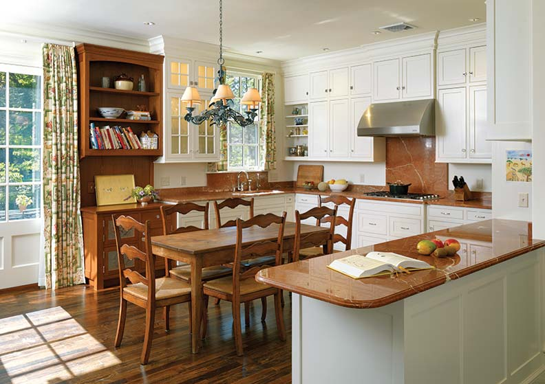 The kitchen is also traditionally inspired with simple recessed panel cabinetry, wood floors, a glass-front cabinet, and a built-in hutch with pie-tin panels.