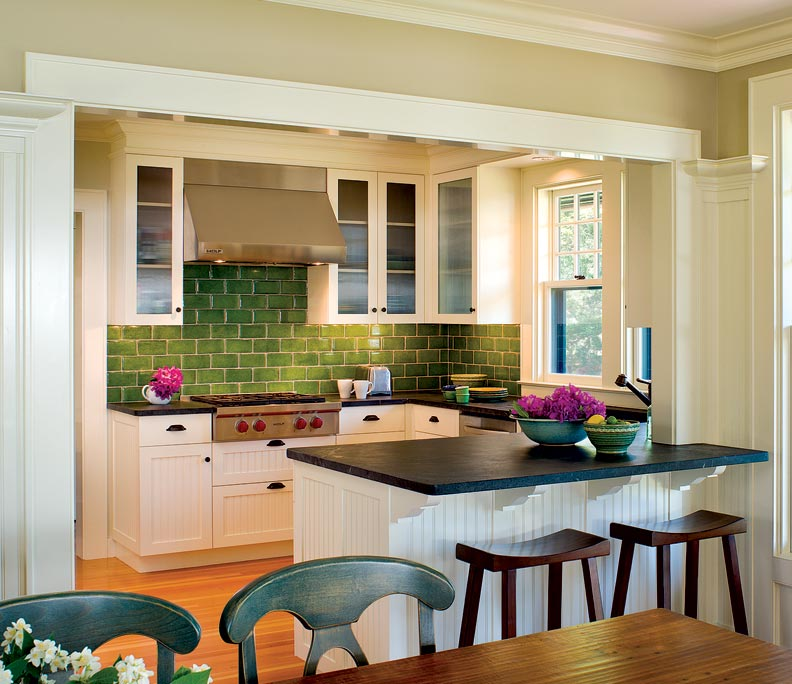 A green subway tiled backsplash contributes to an efficient yet quaint kitchen.