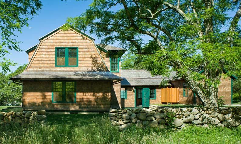 Gambrel gables and elongated soffits help ground this coastal cottage.