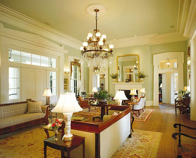 Floor-to-ceiling windows were a common element in Greek Revivals, and in the living room they reach almost to the height of the 15' ceilings. The lighting fixtures are a mix of vintage and new pieces. Sidelights and transom lights set into ornate pediments around the door bring in light and allow views of the river and the wild Southern landscape.
