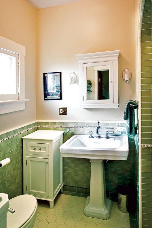 Simple but period-appropriate tile, plumbing fixtures, and lighting highlight a new bath in a former closet.