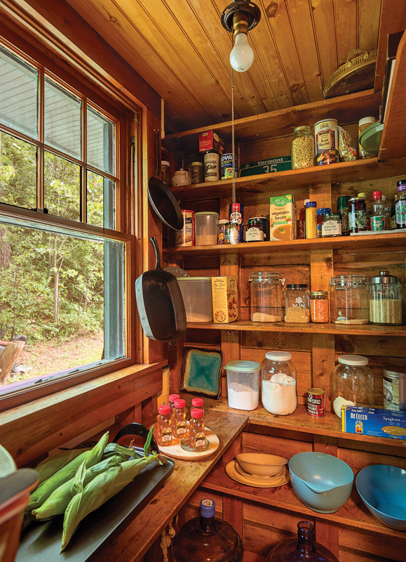 Simple shelves provide generous storage in the country pantry.