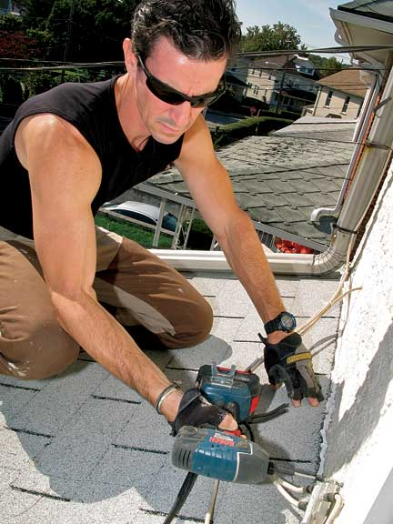 Before ripping off shingles, Mark takes advantage of his rooftop location to tighten up loose cables.