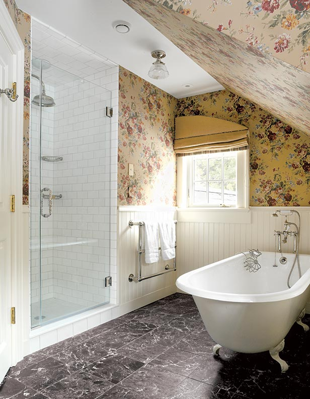 An upstairs bathroom takes advantage of found space. The shower is built into the unfinished attic behind, and its glass door makes the room feel that much bigger. Wallpaper plays up under-the-eaves charm.