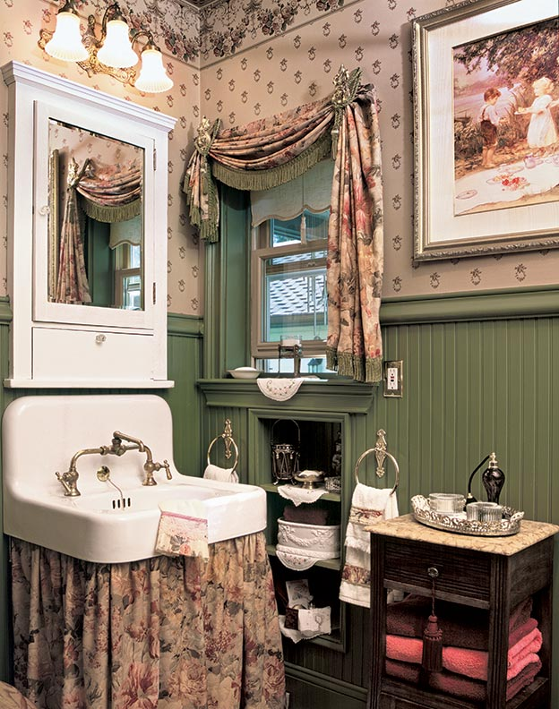 "Every romantic detail in this ""new old"" guest cottage says country Victorian. The wall-hung sink and light fixture are vintage."