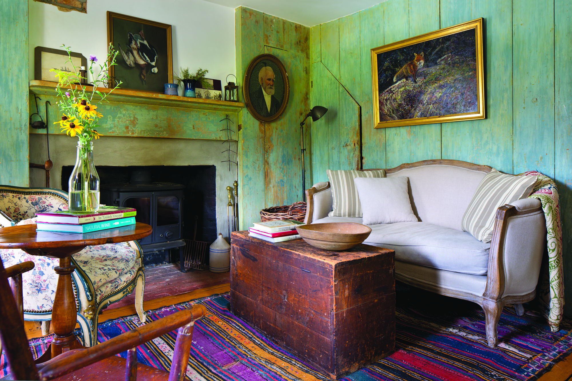 SOUTH PARLOR  On its two interior walls, the old parlor boasts original vertical sheathing still wearing its old blue-green color. The odd door to the left of the sofa leads to the root cellar.