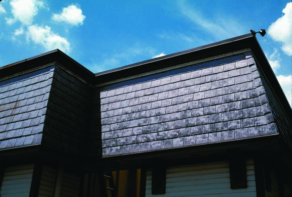 The degrading effects of sunlight, as well as extremes of temperature and moisture, can take their toll on man-made slate as much as any building product. These fiber-cement slates, the modern alternative to the asbestos-cement products popular in the 1920s and '30s, show some fading on an otherwise sound roof. (Photo: James C. Massey)