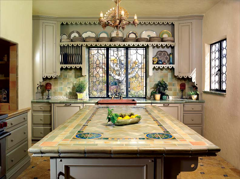 With a tiled island and backsplash, leaded glass windows, and custom-made cabinets, the kitchen is sympathetic to the Spanish Colonial Revival house.