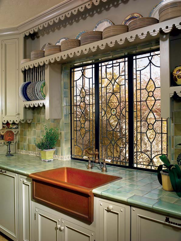 Like many of the kitchen's decorative elements, the copper sink and faucet were eBay finds. Chuck and Judy designed the leaded glass windows themselves.