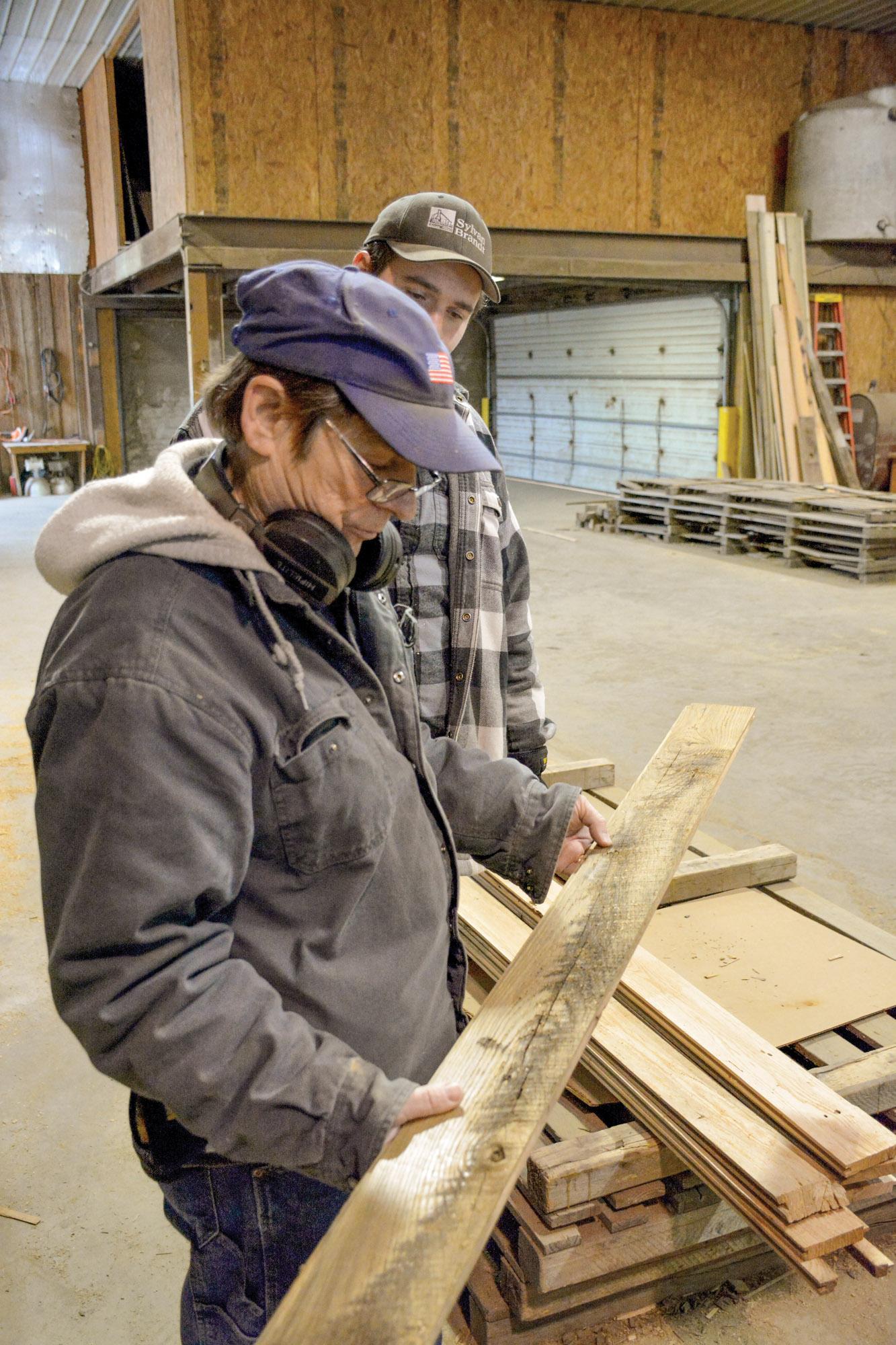 Dean Brandt and associate Robert Walton examine a floorboard before shipment.