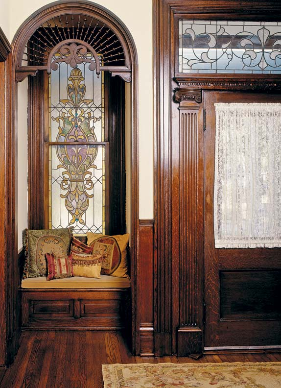 The stained glass window and transom in this Victorian house add beauty and play with streaming light.