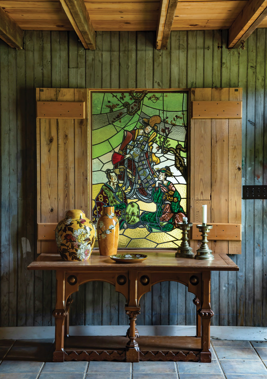 "In the barn, a formal vignette: the Reformed Gothic oak table sits beneath an Aesthetic Movement stained-glass panel inspired by ""The Mikado."""