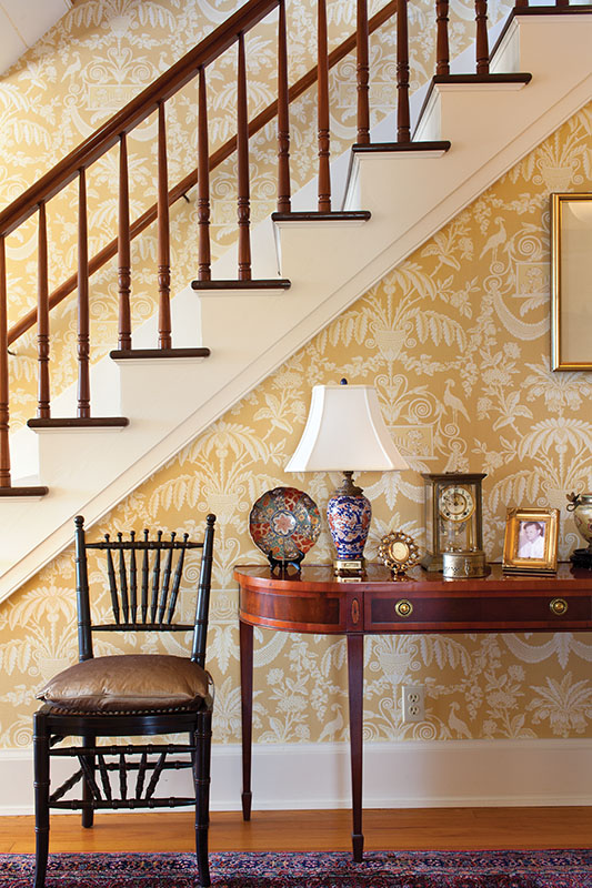 Thibaut Designs' 'Lampas' wallpaper is a suitable scale for the generous stair hall located in the center of the house. Stairs once led to a large ballroom, which has been reconfigured as bedrooms.