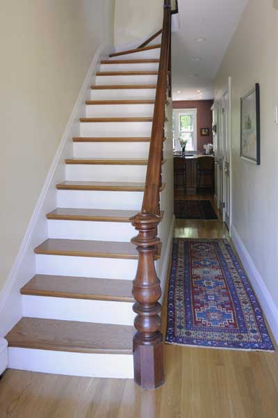 Refinishing the staircase proved to be one of the most challenging aspects of the restoration. After it had been completely stripped, the risers were painted to match the trim, treads were given a natural polyurethane finish, and the railing, balusters, and newel post were stained a rich brown for contrast.