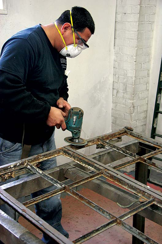 Omar Hernandez works to strip a vintage Hope's casement window down to bare steel. The windows, with steel muntins removed, have been primed and are ready for the installation of the smaller-paned glass inserts with lead caming.