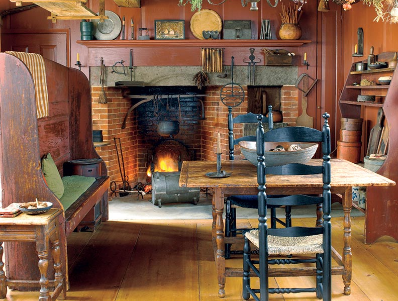 A tall old settle (bench) divides the period-inspired kitchen; the reproduction fireplace is on one side, the modern working kitchen on the other. The settle and table were made in Connecticut in the 18th century.