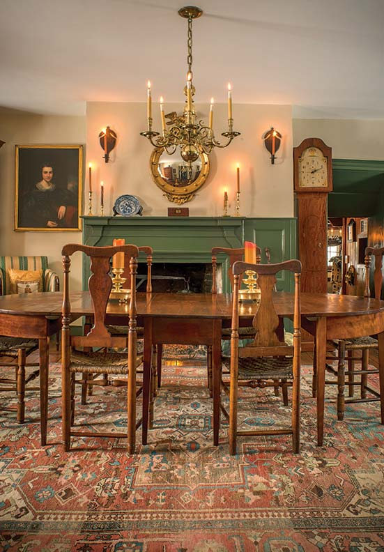 In the dining room, an early 19th-century cherry drop-leaf table with Hepplewhite-style legs is accompanied by a set of eight rush-seated Queen Anne vase-back transitional side chairs, ca. 1810.