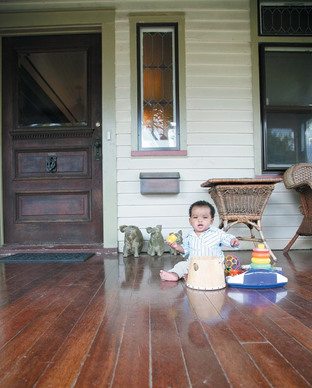 Jack entertains himself on the mahogany porch floor, a project the couple farmed out to contractors after stripping the front door themselves.