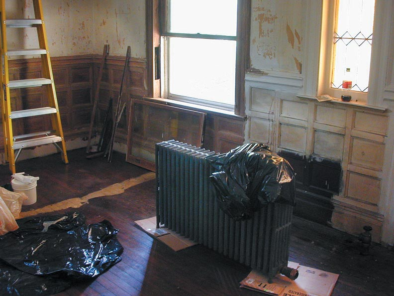 The spot that inspired it all: Original, unpainted wood in a dark stain where the radiator once stood is visible in the living room amid a sea of white wainscoting.