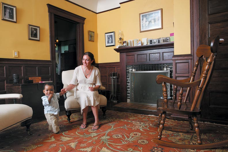 In the living room, Christina and Jack play beside the fireplace mantel Rick rebuilt, one of many projects he completed as Christina removed paint.