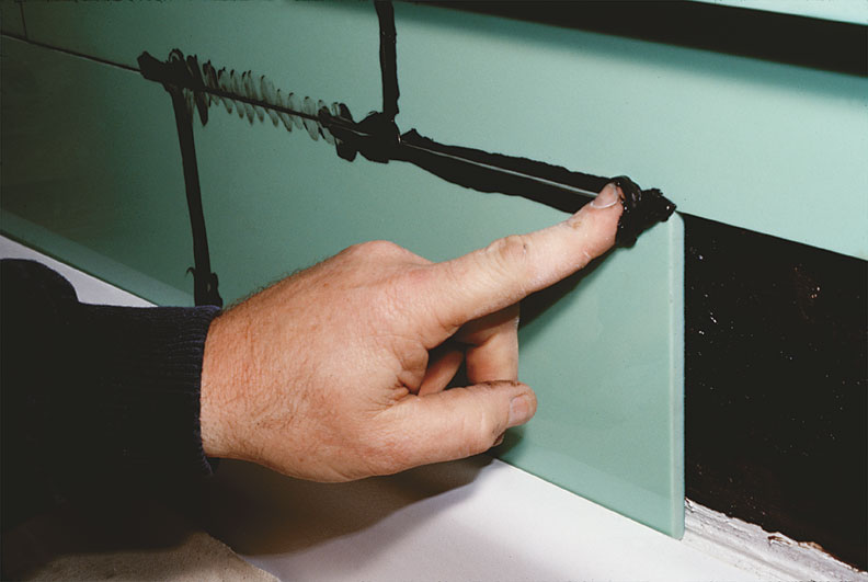You can wipe grout into the narrow space between structural glass tiles using a finger.