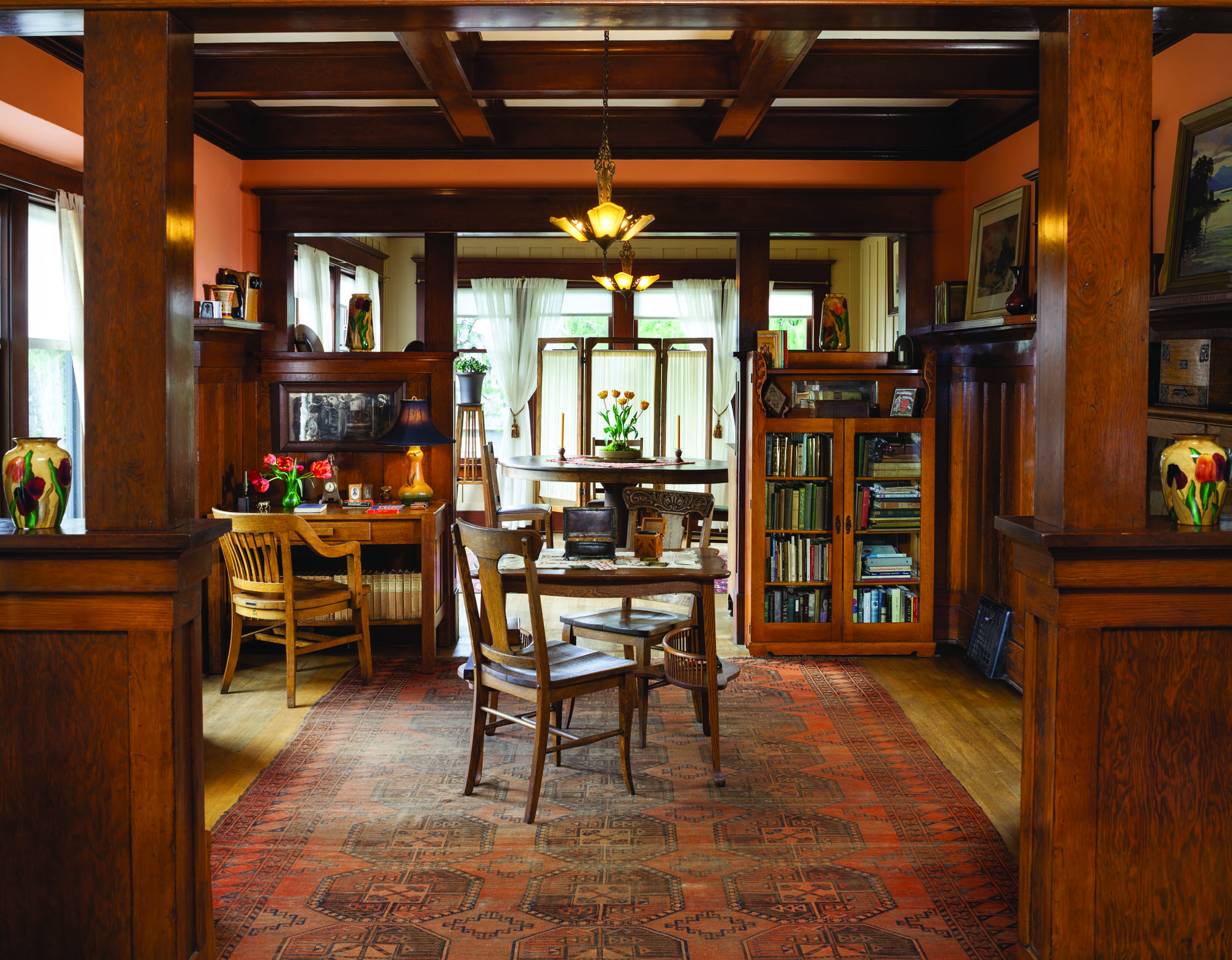 The main spaces flow from the living room to the study and the dining room beyond. Bookcases and desks hold collections of Arts & Crafts ceramics, family mementoes, and vintage books.