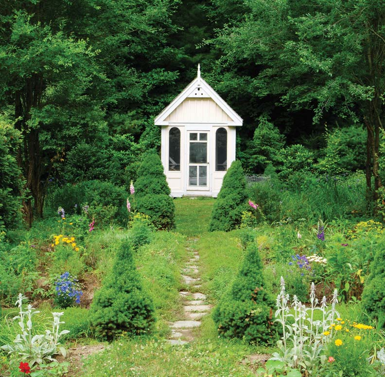 A Victorian-influenced outbuilding is set back to take in views of blooming flowers.
