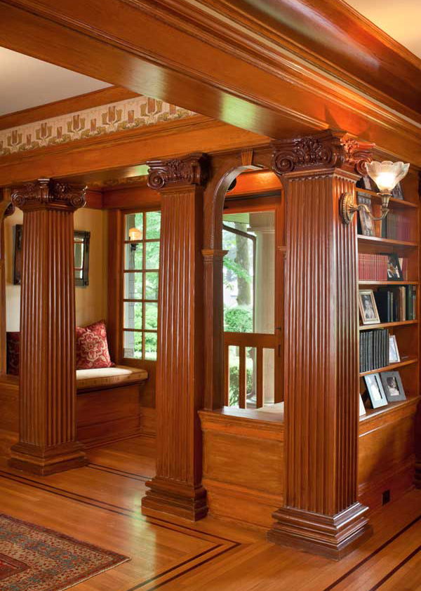Surprising neoclassical columns in mahogany support beams in the entry hall with keystone arches between them, lending a formal air and creating an inviting seating nook.