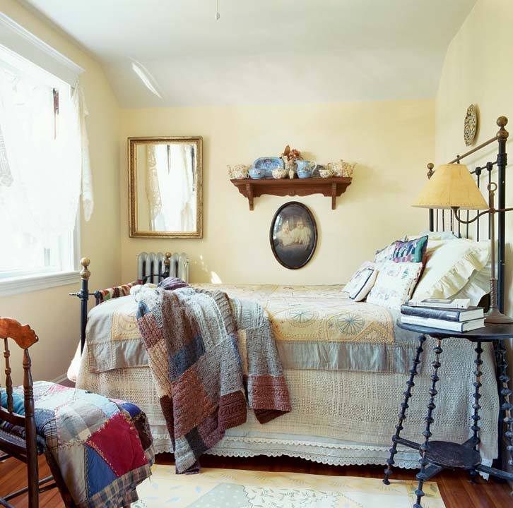 The charming bedroom is centered around an antique brass and iron bedstead. Antique quilts lie on the bed; a collection of vintage tea sets sits on a Victorian wall shelf.