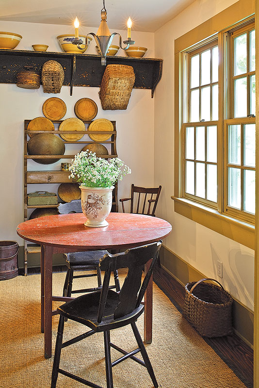 In an 1840 house, a drop-leaf tavern table in original red paint sits on a natural-fiber mat.