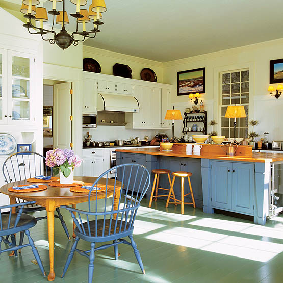 The homeowners wanted a large kitchen for entertaining. Tate divided the space into an eating area and a food prep area. The kitchen's island offers loads of storage and preparation space as well as an additional sink. The island countertop is finished in a warm wood tone while its cabinets are painted a Colonial blue.
