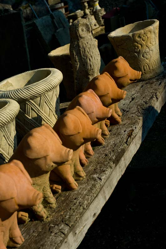 Terracotta pigs and cement containers await sale.