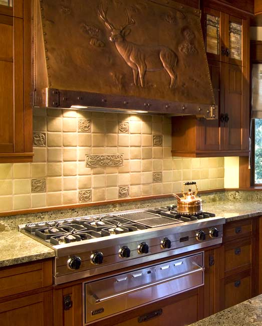 The 200-pound copper range hood is by Archive Designs; a deer theme continues on custom-made tile.