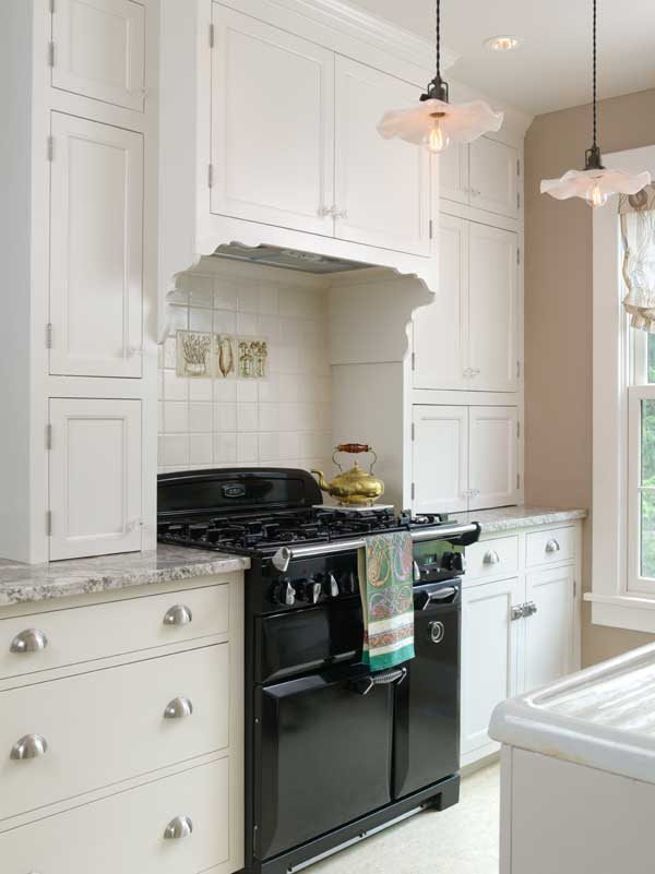 The author wanted shallow cupboards on either side of the stove to create an old-fashioned cooking alcove; resting on the countertop, cupboards also hide small appliances.