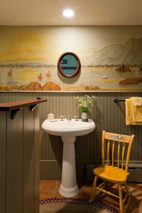 The bathroom mural was inspired by Hudson River School paintings. The arrowback child's Windsor chair was redecorated by Fred Angier's mother, Libby.