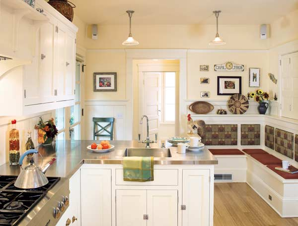 The crisp new kitchen has cabinets finished with 'Buttermilk' from Benjamin Moore; originial wainscot was reused in building the upholstered banquette. Photo: William Wright.