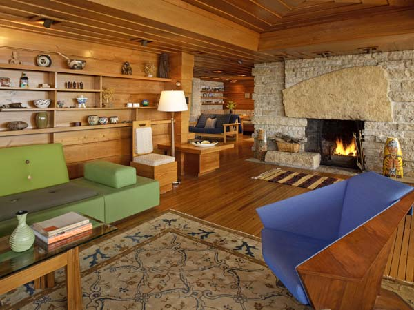 The fireplace includes a massive boulder with stone from the reopened quarry. Note the original built-in end table; the dining area and family sitting room are in the background.