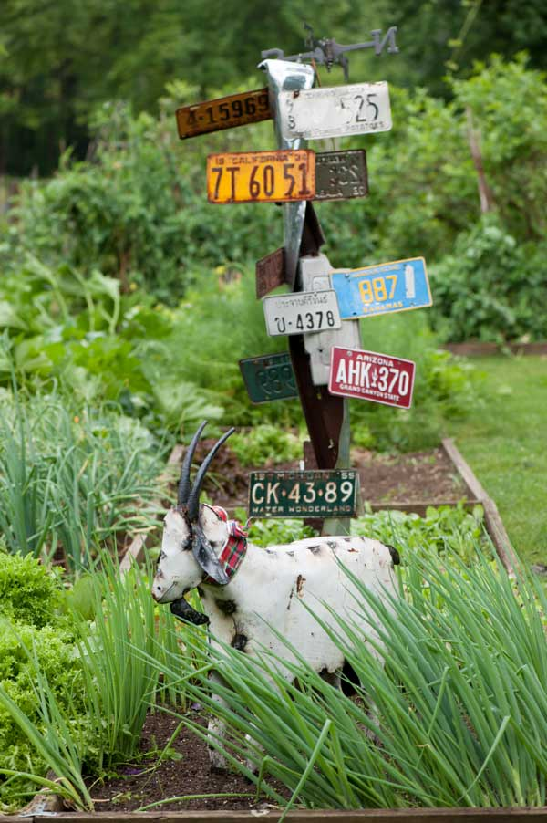 "The focal point of the food garden is a ""sculpture"" of license plates from all the places the couple has lived."