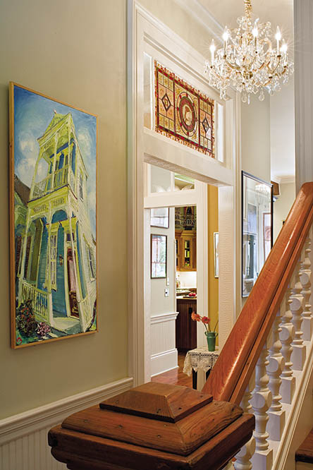 The front entry hall opens to the front parlor and dining room to the left with a stair to the second floor on the right. The stair balusters and newel post are from a New Orleans salvage yard. On the left is a painting of a double-gallery house by New Orleans artist James Michalopoulos. The stained-glass transom above the dining entry is a late nineteenth-century piece.