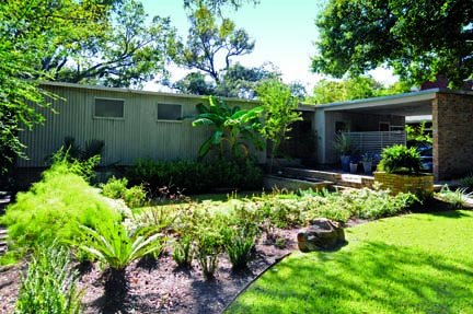 The front façade of the house features distinctive corrugated asbestos tiles. Mark and Jeff added landscaping features to create a more inviting entry.