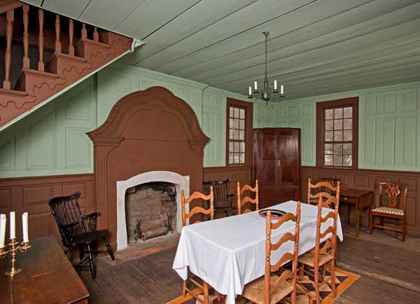 The great room boasts paneling, dentil molding in the cornice, and a unique fireplace treatment.