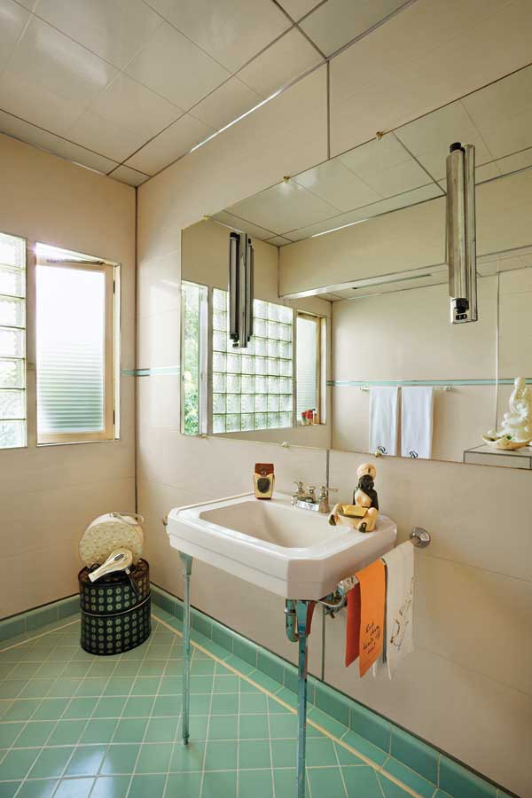 The guest bathroom is all original: large mirror with lighted sconces, glass block flanked by a casement window, fixtures, Marlite walls, and turquoise tiles.
