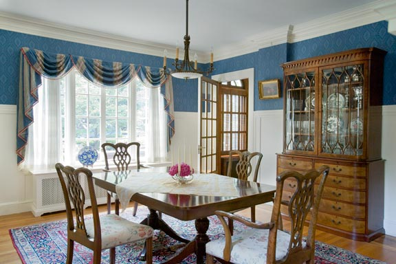 The interior design process began in Charlotte's dining room, because she already had furnishings appropriate for the space; sapphire-blue wallpaper was inspired by the tones in the Persian rug.