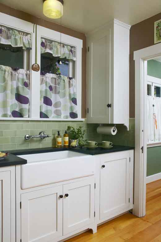 The kitchen boasts stylish white cabinets, built-ins, and original light fixtures.