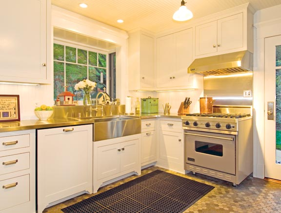 "The kitchen, in white and stainless steel, captures the look and spirit of ""sanitary"" kitchens of the early 20th century."