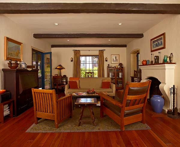 The living room retains its rustic hewn beams and pegged mahogany floor. Between a Stickley Bros. Cube Chair and a Stickley Bros. armchair sits a California tile-top table.