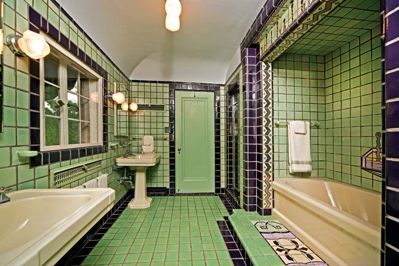 The master bathroom is entirely original, and sports a separate shower and tub, double sinks, and Art Deco flourishes on its tiles—like the pastel bath mat and wall decoration, and the iridescent gold zigzag border.